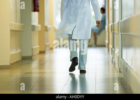 Médecin homme walking in hospital corridor, cropped vue arrière