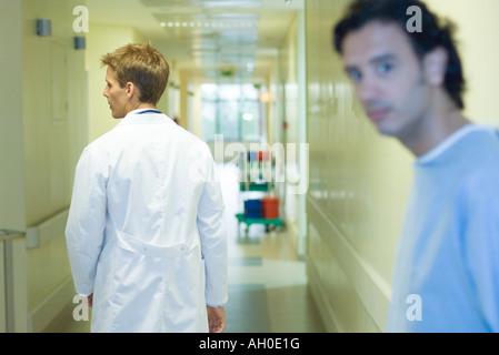 Médecin homme walking in hospital corridor, vue arrière, man looking at camera en premier plan