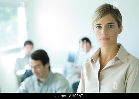 Young businesswoman looking at camera, tête et épaules, associés en arrière-plan Banque D'Images