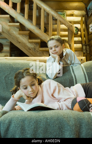 Girl on couch reading book, boy looking over shoulder Banque D'Images