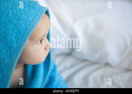 Bébé enveloppé dans une serviette, looking away Banque D'Images