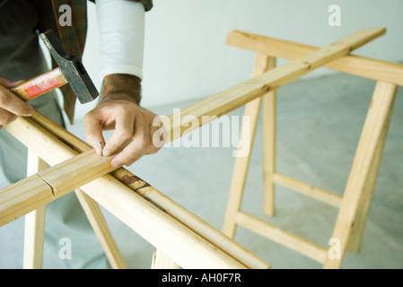 Man hammering clou dans la planche en bois, cropped view Banque D'Images
