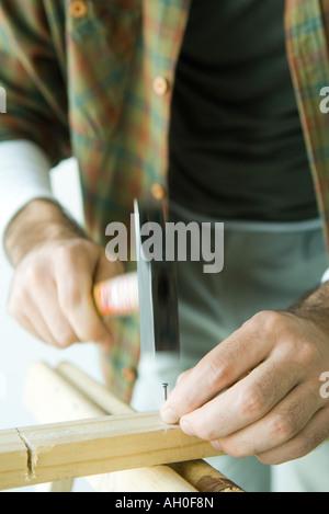 Man hammering nail en bois, cropped view Banque D'Images