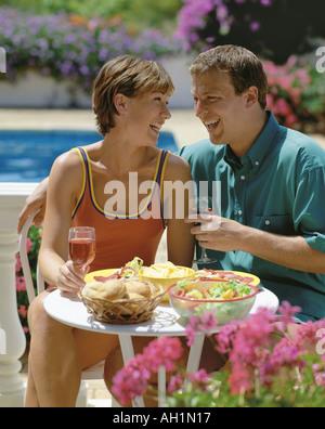 Young couple manger et boire sur la terrasse près de la piscine