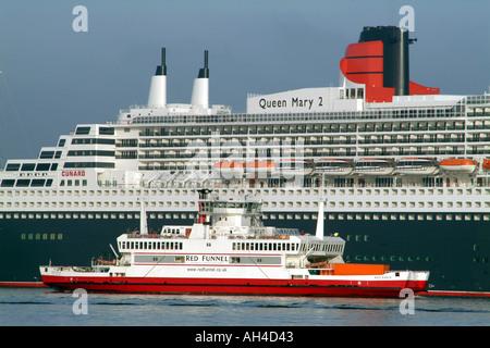 Queen Mary 2 sur Southampton Water aux côtés dérisoires est rouge rouleau entonnoirs sur roll off Red Eagle navire Banque D'Images