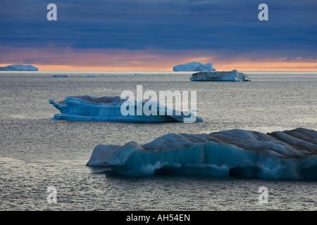 Les icebergs, sur une mer calme contre une leaden gris bleu ciel de coucher du soleil dans le détroit de Davis, Banque D'Images
