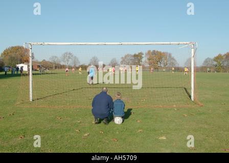 Père & Fils & ball derrière poteau de but regardant teen kids playing football match village jeu de soccer père vivre ensemble avec collage enfant UK