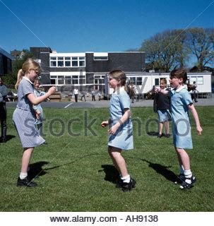 Ecolières dans saut aire de jeux de l'école primaire à l'île de Man UK Banque D'Images