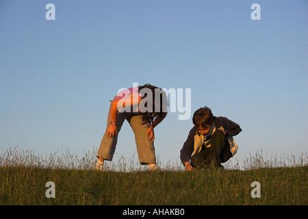 10 ans garçon et fille étudier quelque chose d'intérêt sur une banque d'herbe.