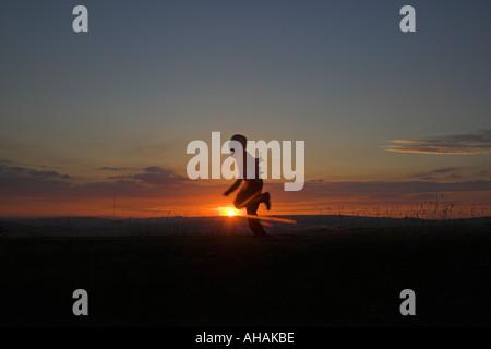 Silhouette d'un garçon de 10 ans, fonctionnant avec le soleil en arrière-plan. Banque D'Images