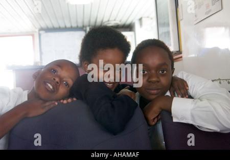 Trois enfants en uniforme de l'école d'Afrique du Sud sur le ferry à l'école à Robben Island Banque D'Images