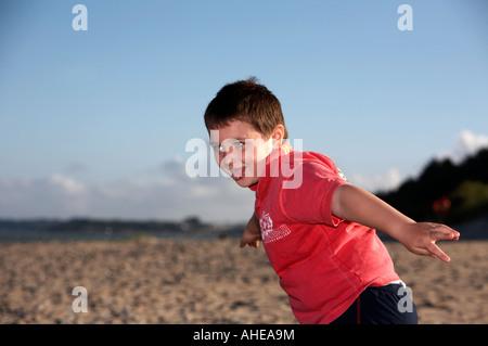 Six ans portant des T-shirt et collant sa langue dehors avec bras ouverts jouant sur la plage, dans le comté de Banque D'Images