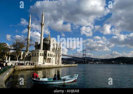Les hommes en petit bateau et Mosquée Ortakôy sur les rives du Bosphore, Istanbul, Turquie Banque D'Images