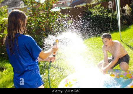 Teenage girl and boy éclaboussant mutuellement avec les tuyaux d'eau dans le jardin Banque D'Images