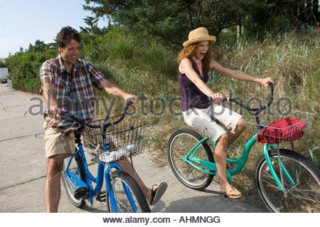 Couple riding bicycles sur chemin de plage Banque D'Images