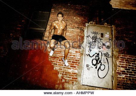 Saut à l'athlète masculin contre le mur de brique Banque D'Images