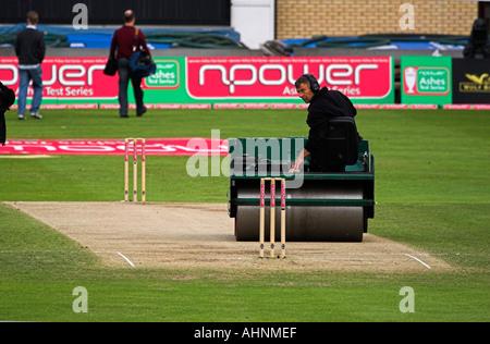 Homme de rouler le terrain de cricket en préparation pour un jeu, en Angleterre