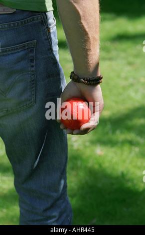 Homme tenant une boule rouge dans sa main.