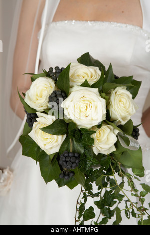 Young bride holding bouquet, mid section, close-up Banque D'Images