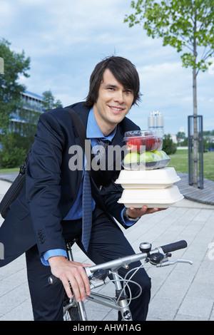 Businessman in park en vélo avec beaucoup de rire lunch. Banque D'Images
