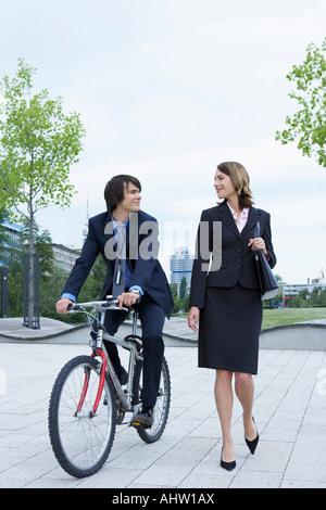 Businessman and Woman talking elle est lui marche sur le vélo en riant. Banque D'Images
