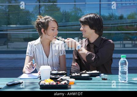 Couple eating sushi ensemble à l'extérieur tout en travaillant. Banque D'Images