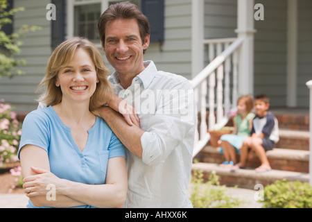Couple hugging avec enfants en arrière-plan Banque D'Images