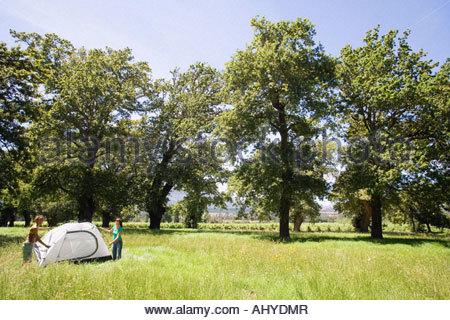 Deux jeunes femmes se tenant debout au milieu de l'assemblage à distance sur tente dôme camping Woodland clearing Banque D'Images