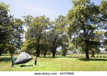 Jeune couple standing in distance milieu assemblage tente dôme camping dans le défrichement des terres forestières Banque D'Images