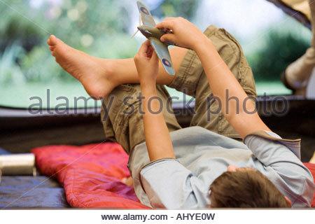 Boy 810 couché sur un sac de couchage à l'intérieur de tente sur jardin pelouse Playing with toy aero avion vue Banque D'Images