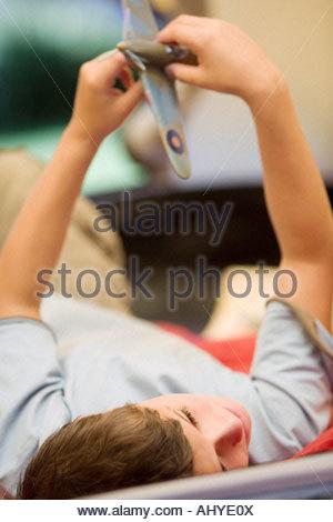 Boy 810 couché sur un sac de couchage à l'intérieur de tente sur jardin pelouse Playing with toy avion aero inclinaison Banque D'Images