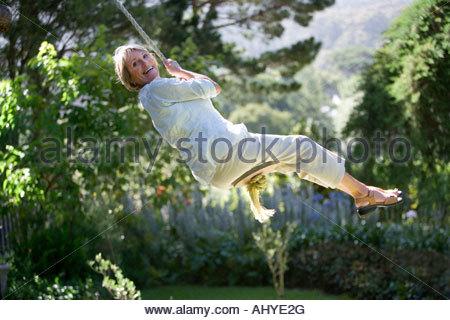 Senior woman swinging sur corde côté jardin swing smiling woman Banque D'Images
