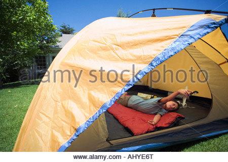 Boy 810 couché sur un sac de couchage rouge orange à l'intérieur de tente sur jardin pelouse Playing with toy aero Banque D'Images