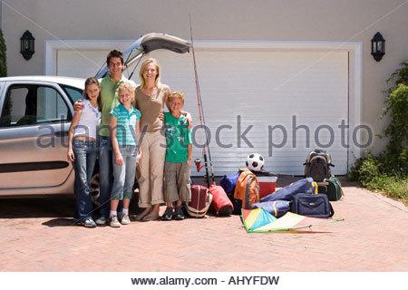 Debout à côté de la famille voiture garée avec équipement de camping près de l'open boot on driveway smiling portrait Banque D'Images