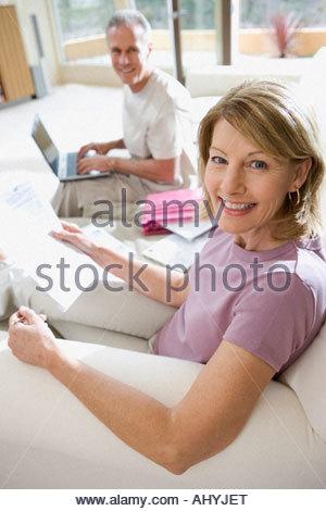 Senior man sitting on sofa at home, à l'aide d'ordinateur portable, l'accent sur mature woman holding projets en Banque D'Images
