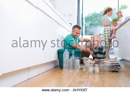 30 ans en couple, fille et garçon les enfants âgés de 6 dans la cuisine avec des bouteilles, bidons et des journaux Banque D'Images