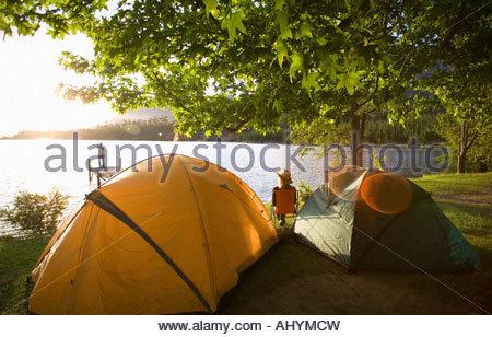 Young woman relaxing on voyage de camping près de deux tentes dôme au bord du lac au coucher du soleil, regarder Banque D'Images