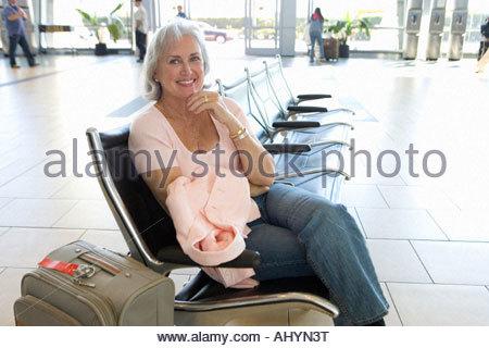 Senior woman sitting in airport lounge, holding départ dossier rose, smiling, portrait, portrait Banque D'Images