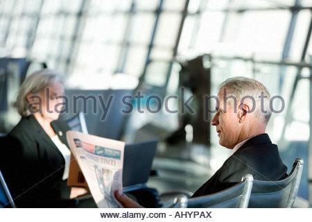 Businessman and woman sitting in airport departure lounge, man, l'homme la lecture de la presse financière, side Banque D'Images