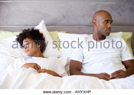 Jeune couple dans le lit, à l'un de l'autre Banque D'Images
