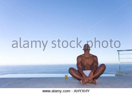 Jeune homme assis en tailleur sur le sol à l'extérieur par la mer, jusqu'à Banque D'Images