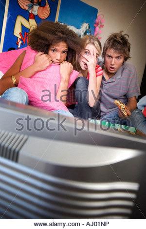 Trois amis adolescents regarder la télévision avec des expressions sur des visages effrayés, la télévision en premier Banque D'Images