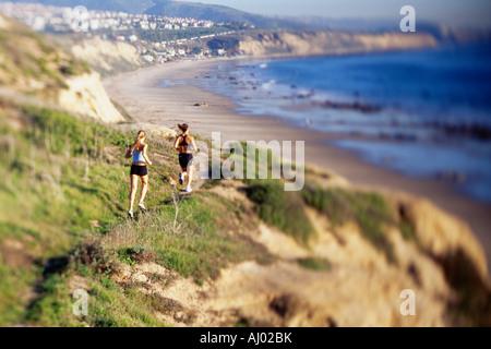 Women jogging sur l'eau le long de la falaise Banque D'Images