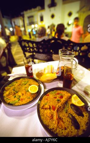 Repas de la Paella et de la sangria dans un restaurant en plein air sur la Plaza del Socorro de nuit, Ronda, Andalousie, Banque D'Images