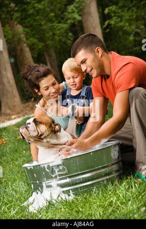 Caucasian family avec petit garçon Bulldog Anglais donnant une baignoire en plein air Banque D'Images
