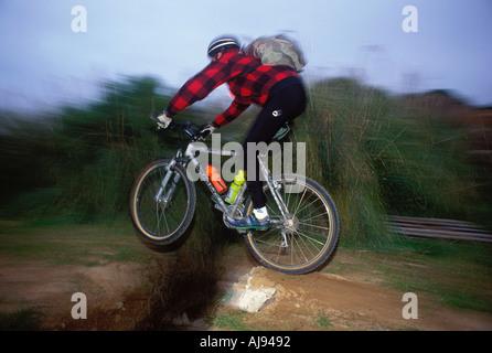 Un vélo de montagne sautant par-dessus un fossé sur un sentier singletrack Banque D'Images