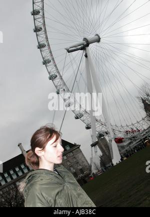 Teenage girl in parka en face du London Eye Banque D'Images