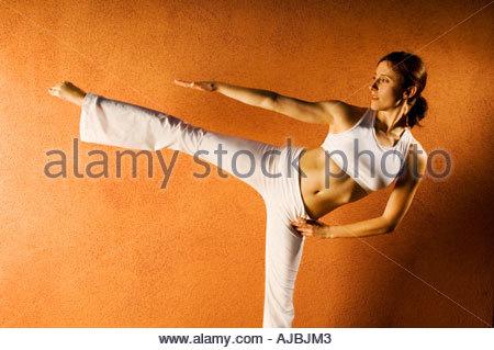 Femme forte, équilibre Yoga pose avec force l'équilibre de beauté et de grâce en face de couleur terre cuite mur Banque D'Images