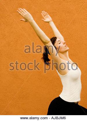 Femme adulte en Yoga comme étirer posent avec force la beauté de l'équilibre et la grâce en avant du mur de couleur Banque D'Images