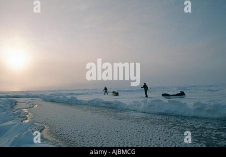 Groupe de ski sur route verglacée au coucher du soleil Banque D'Images